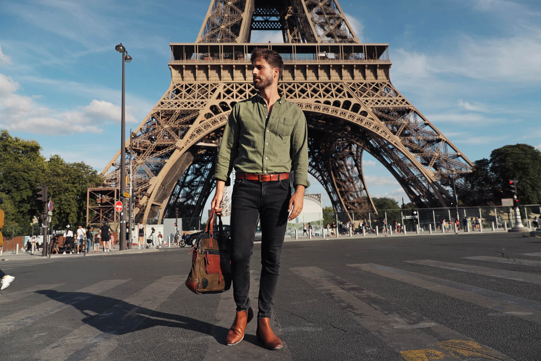 Man standing in front of Eiffel tower holding a leather bag and wearing a leather belt