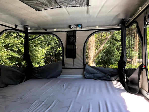 interior of james baroud roof top tent showing open panoramic windows and built in mattress