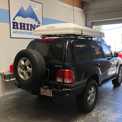 Toyota Landcruiser 100 Series with newly installed roof rack and white iKamper Skycamp Roof Top Tent bought in California