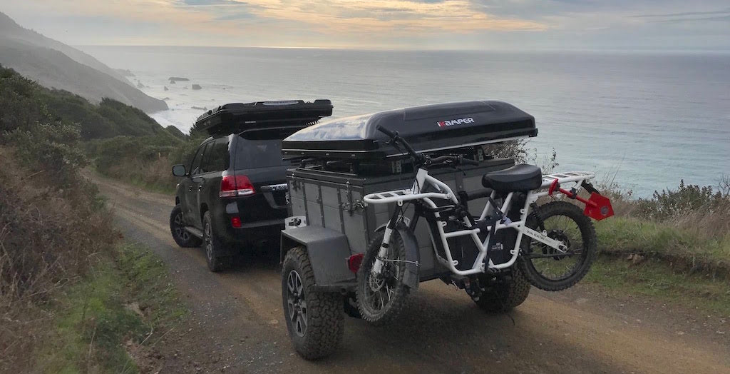 ubco 2x2 electric adventure bike with off road trailer and kitted out overlanding truck