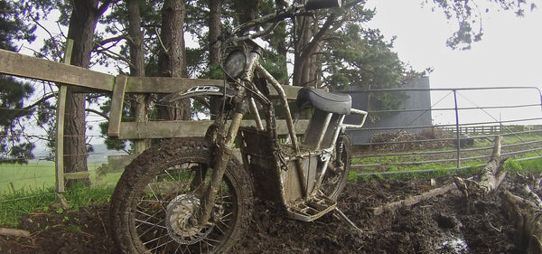 ubco 2x2 electric dirt bike covered in dirt