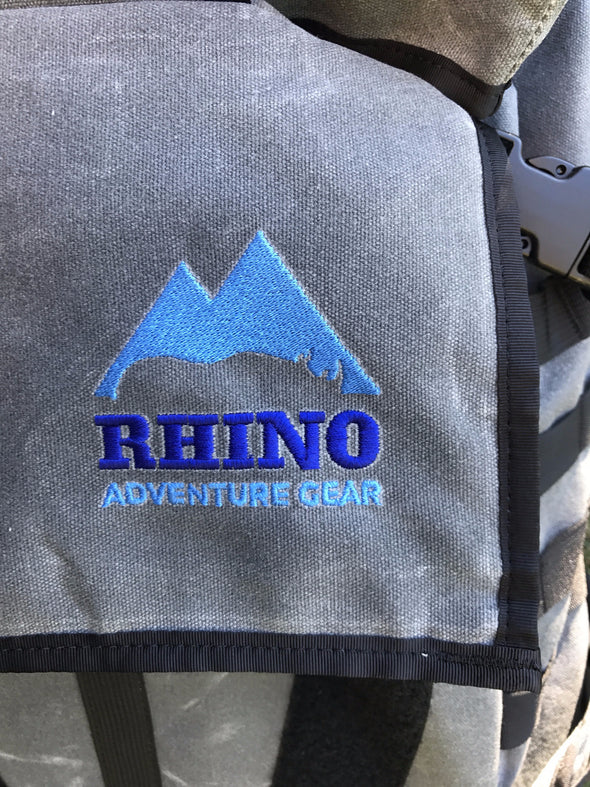 Detail of embroidered Rhino Adventure Gear logo stitched onto top flap of Adventure Backpack