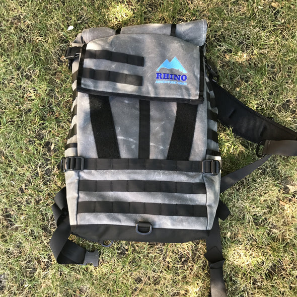 Adventure Backpack with Rhino Adventure Gear embroidered logo laying on the grass