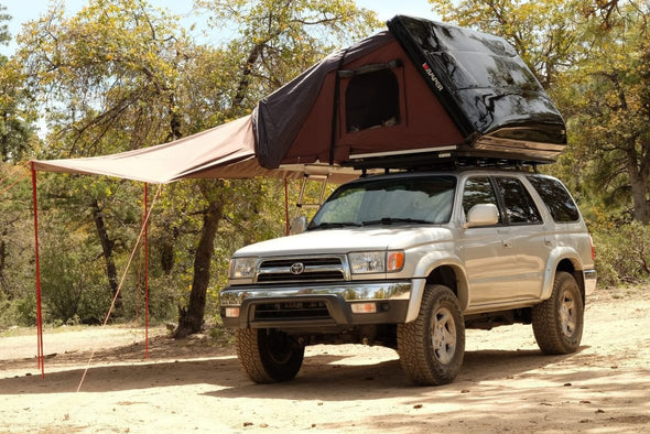 iKamper Skycamp roof top tent shown with awning extension. Awning is supported by two vertical poles and is staked into ground.