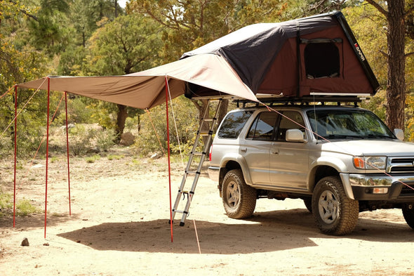 iKamper Skycamp roof top tent awning shown from passenger side of vehicle with awning extending over roof top tent ladder area