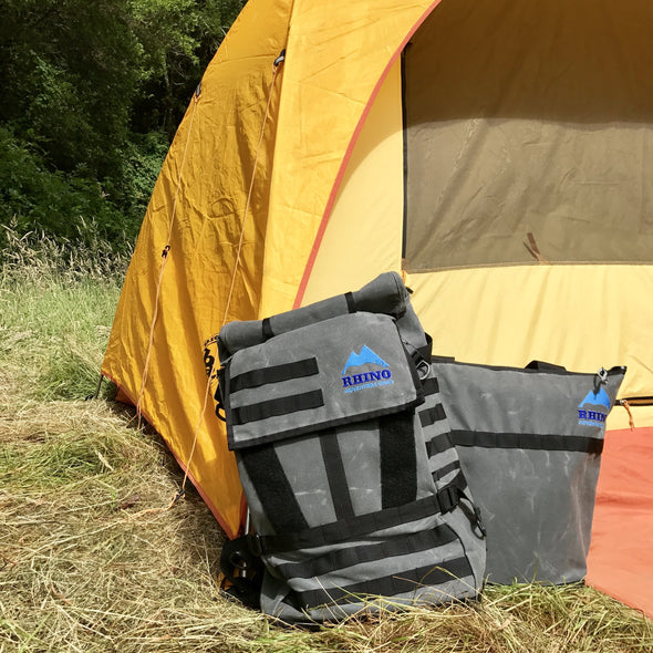 Adventure Tote Bag and Adventure Backpack, both grey with black trim and blue Rhino Adventure Gear logo shown leaning against yellow and orange tent
