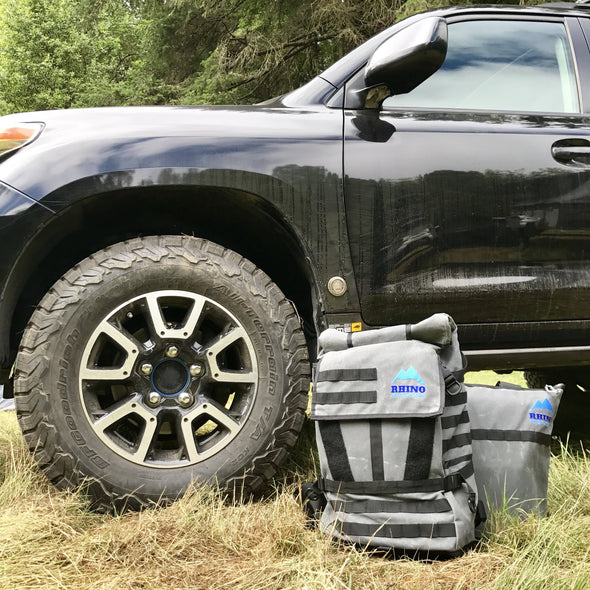 Adventure Backpack and Adventure Tote Bag with Rhino Adventure Gear embroidered logo leaning against black Toyota Landcruiser near wheel