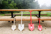Family of four USA-made Shelterwerks welded aluminum shovels leaning against picnic table
