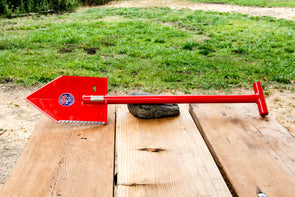 Red MPS-1 Shelterwerks emergency shovel pictured laying across wooden picnic table