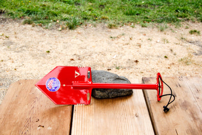 Red MPS-2T Shelterwerks compact emergency shovel pictured laying across wooden picnic table