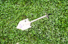 Beige MPS-2T Shelterwerks compact emergency shovel pictured laying in grass field