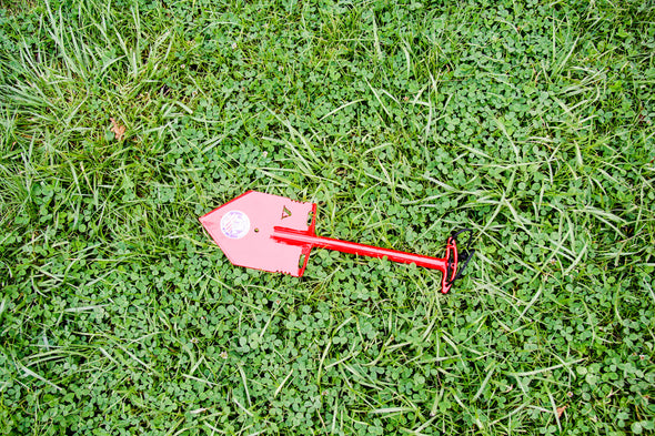 Red MPS-2T Shelterwerks compact emergency shovel pictured laying in grass field