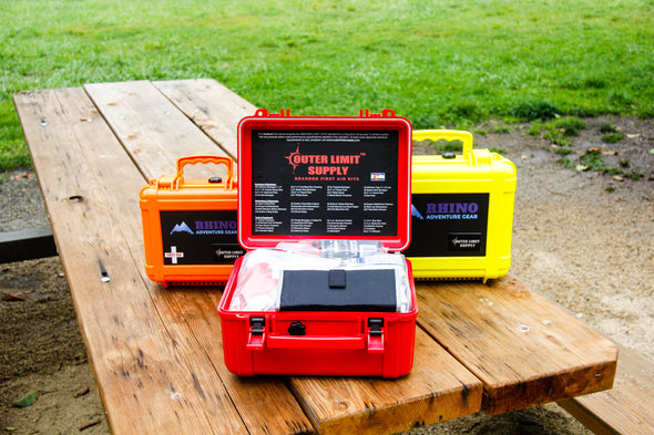 Three types of trauma kits for off road travelers, shown with red outback first aid kit opened on picnic table