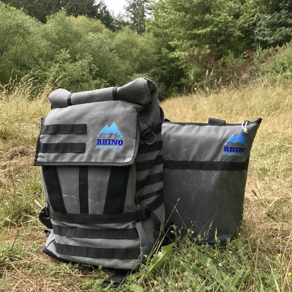 Adventure Tote Bag and Adventure Backpack, both grey with black trim and blue Rhino Adventure Gear logo shown sitting in grassy field