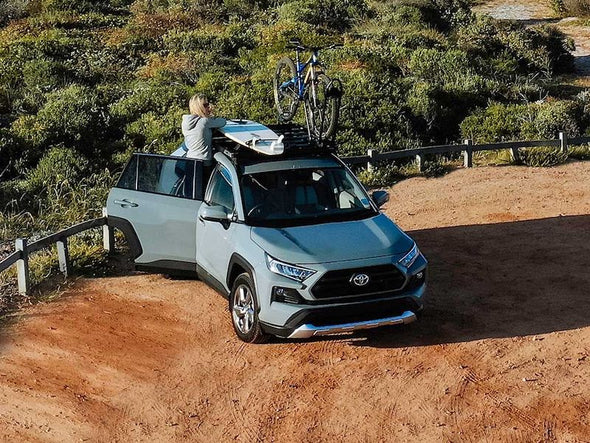 Front Runner SlimLine II Roof Rack Kit on 2019 Toyota Rav4 with woman mounting surfboard and mountain bike to roof rack
