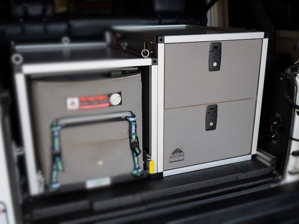 Goose Gear stacked double drawer shown in gray next to fridge freezer in rear cargo of overland rig