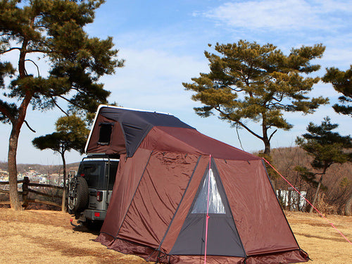 Annex room ground enclosure extension for iKamper Skycamp roof top tent. The annex room is shown zipped onto the door of the iKamper roof top tent and extends at ground level adjacent to the vehicle