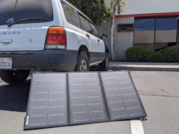 Merlin Solar BXD95 trifold portable solar panel shown deployed next to white Subaru