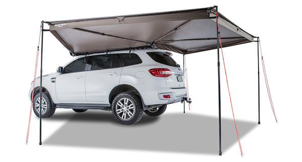 Left Side Mounted Rhino Rack Batwing Awning shown set up with 4 legs extended and tie downs staked in ground