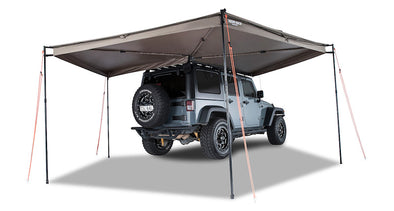 Right Side Mounted Rhino Rack Batwing Awning shown set up with 4 legs extended and tie downs staked in ground