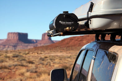 Road shower 4 mounted alongside roof top tent on roof rack with scenic western landscape in background
