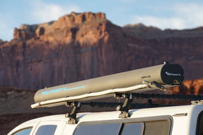 Road Shower 4L solar heated camping shower mounted on vehicle roof rack with scenic red rock landscape in background