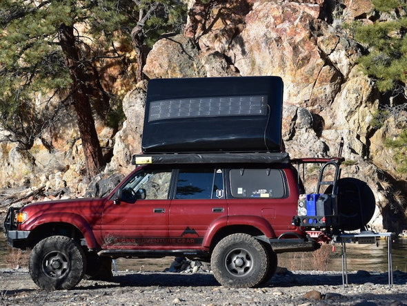 Red Toyota Landcruiser 80 series with black iKamper Skycamp roof top tent outfitted with SolarHawk overlanding solar panels