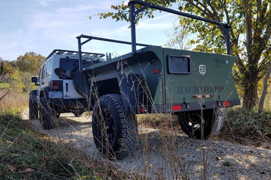 Off Road Overland Trailer with heavy duty rack system on trail behind Jeep