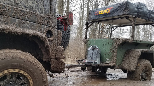 Muddy off road trailer with overhead rack system and roof top tent
