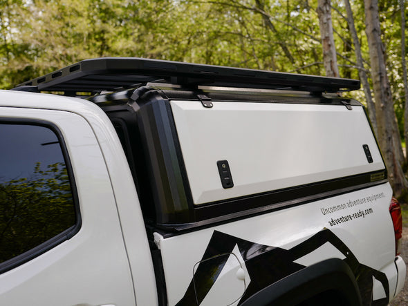 Side view of Toyota Tacoma truck cap by RLD Designs shown with optional platform rack system added