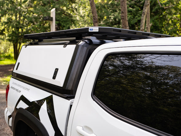 Side view of RLD stainless steel truck topper for Toyota Tacoma shown in black with white doors