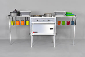 Trail Kitchen Camp Kitchen with Integrated Stove shown assembled with cookware and camping dinnerware on sturdy table and shelving