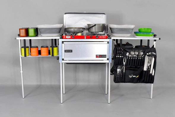 Trail Kitchens Compact Camp Kitchen assembled with camping cookware and dinnerware stowed on shelving