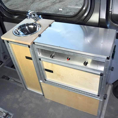 Trail Kitchens Van Kitchen installed behind passenger seat in sprinter van shown with detachable kitchen unit in place next to sink