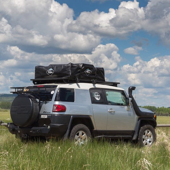 FJ Cruiser with Treeline Roof Top Tent stored in black travel bag on roof of vehicle