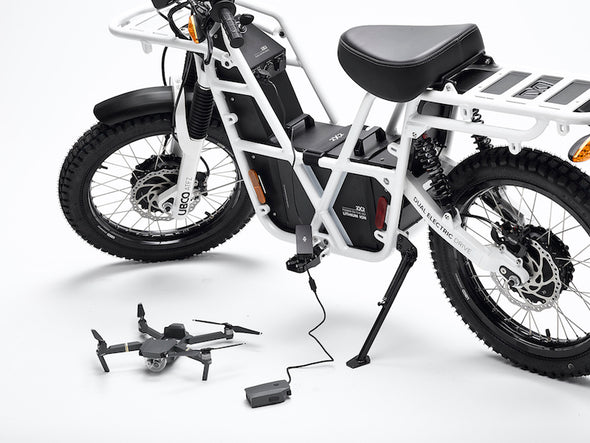 Recharging a drone using the portable battery pack equipped on Ubco 2x2 utility off road bikes
