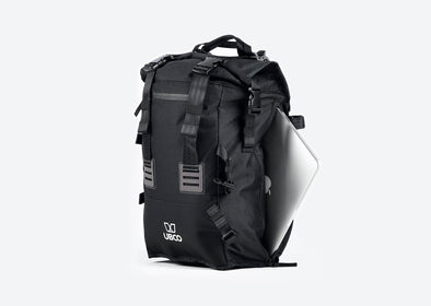 "Black Pannier Backpack compatible with Ubco 2x2 Pannier Racks shown with a laptop being slid into the 15"" laptop compartment"