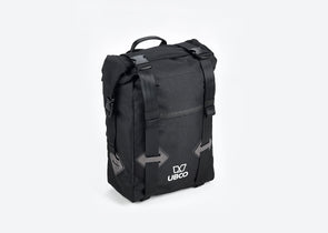 Diagonal view of Ubco 2x2 Pannier Bag. Pannier bag is thick black polyester with a handle on top and two wide vertical straps that buckle on the top and there is a small white Ubco logo branding near the bottom of the bag.