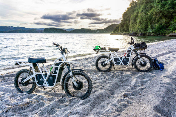 Ubco 2x2 off-road electric adventure bikes available at Rhino Adventure Gear shown riding through sand on beach