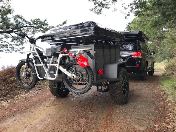 ubco 2x2 2017 off road electric adventure bike from Rhino Adventure Gear shown mounted on bike rack behind off road trailer during overlanding trip