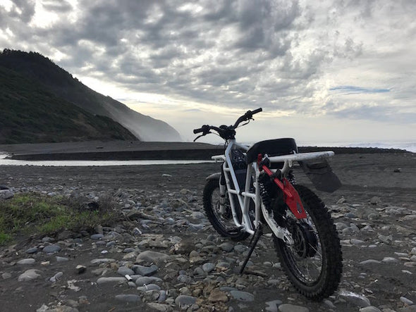 ubco 2x2 2017 off road electric adventure bike from Rhino Adventure Gear shown on sandy beach overlooking california coastline