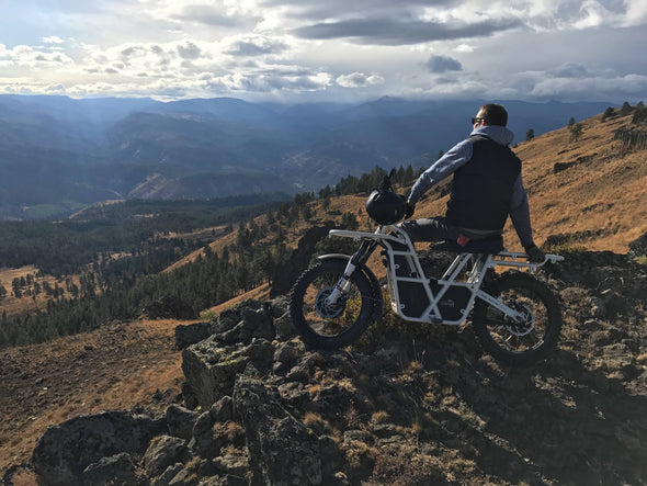 Ubco 2x2 off-road electric adventure bike available at Rhino Adventure Gear shown overlooking scenic vista