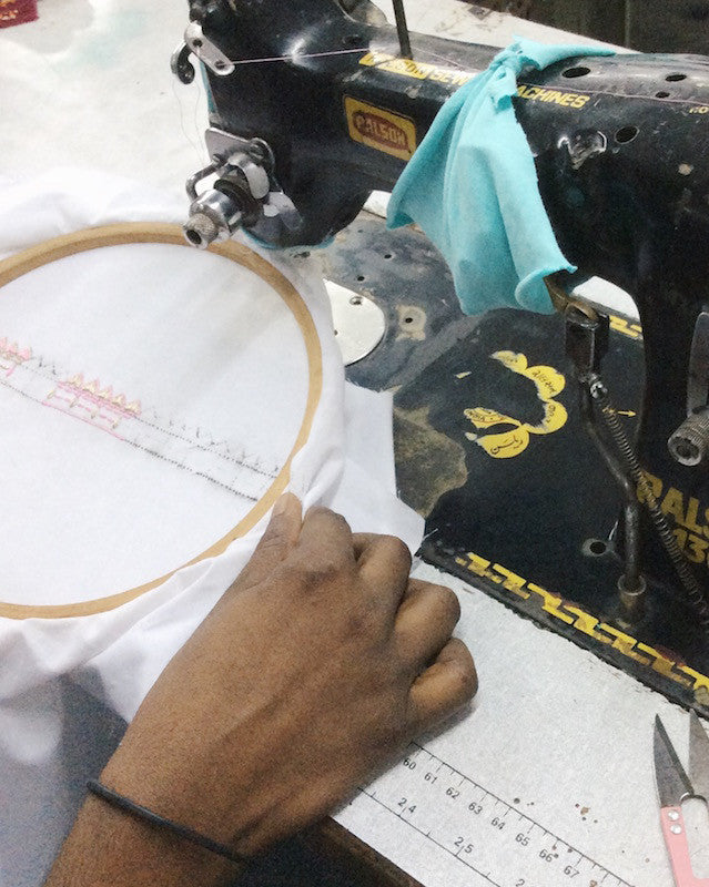 Master-ji behind the machine testing out embroidery patterns