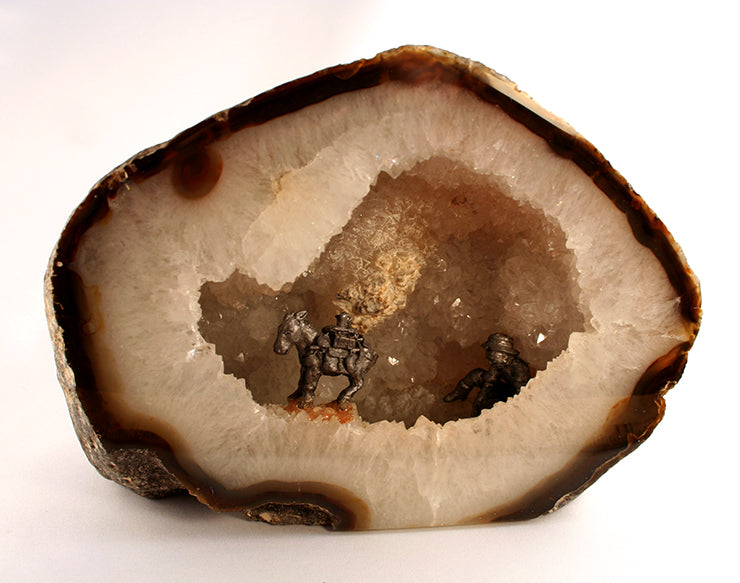 Agate half with open hollow filled with crystals and pewter figures