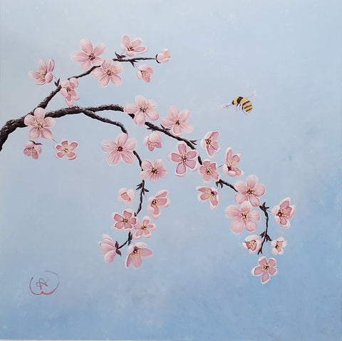 pink blossoming fruit tree branch on blue background with bumblebee