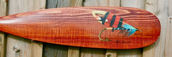 Image shows the tip of a red wood paddle on which there is painted a fish hook with a bright blue feather, specifically a Dark Ranger Salmon Fly. By Nova Scotia artist Peter Gough.