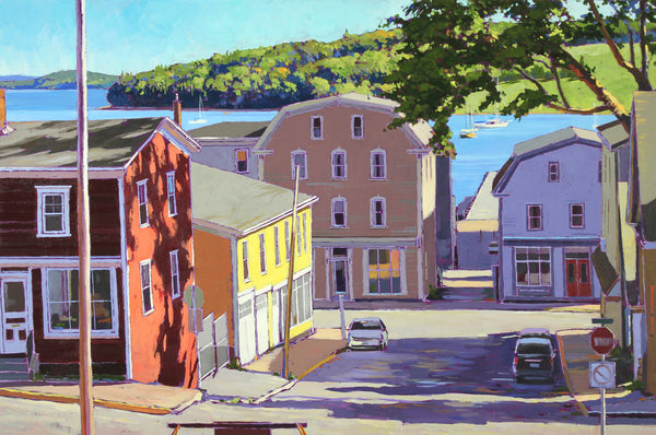 looking down a sunny street towards Lunenburg harbour with sailboats in the water