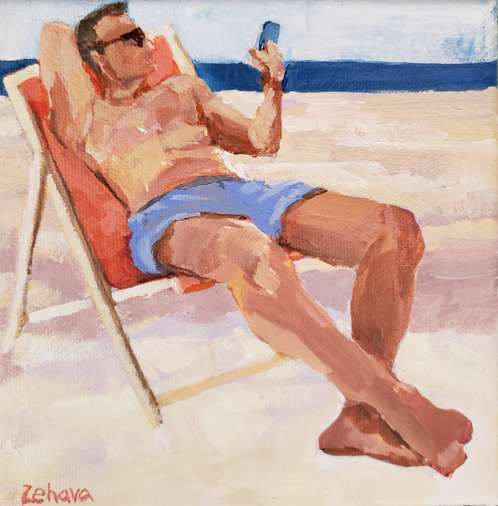 man in blue bathing suit lounging on a beach chair looking at his phone