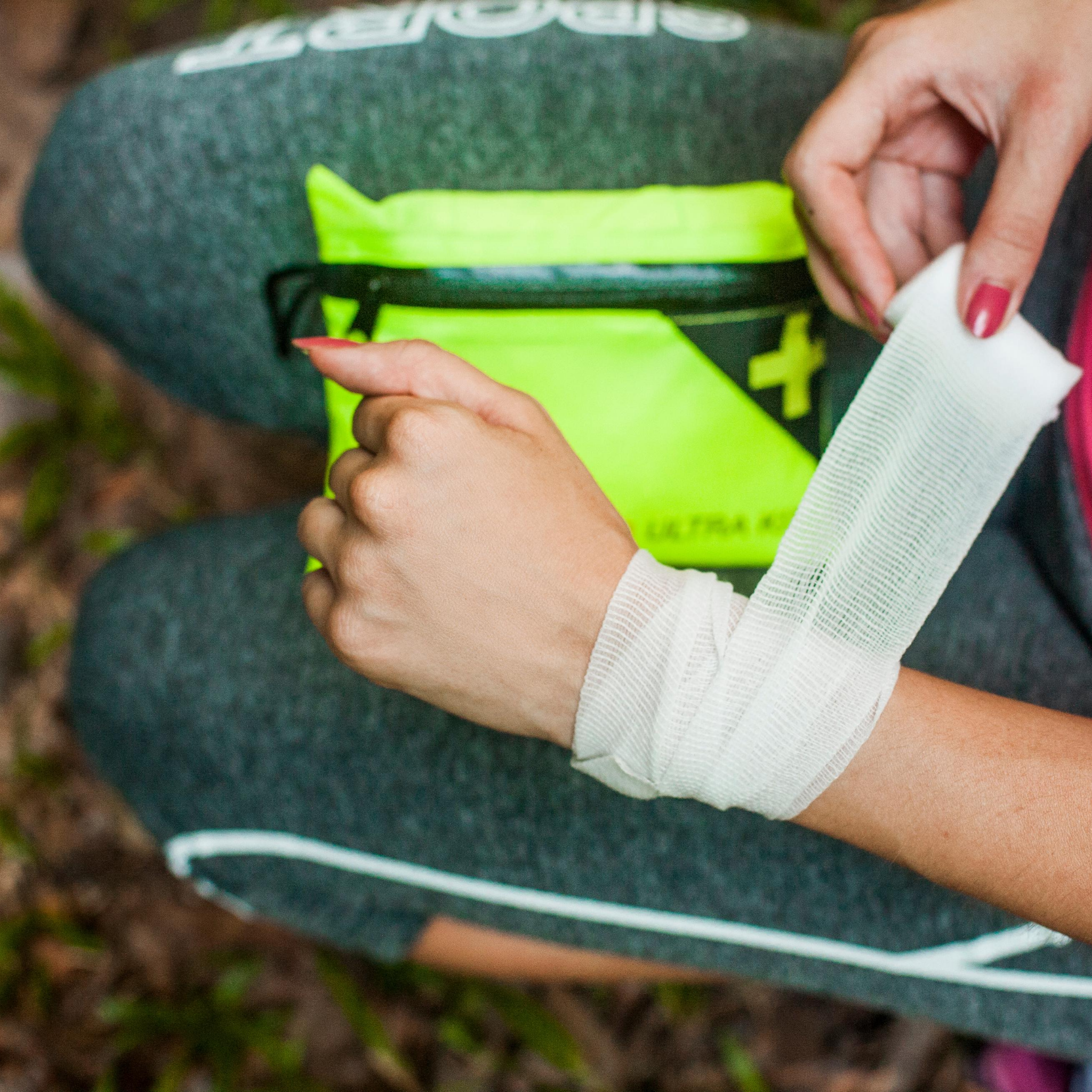 Injured women wrapping wrist with a compression bandage from the TrailSurvivor Ultra Kit