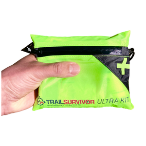 Hand Holding TrailSurvivor Ultra Kit a Lightweight Survival & First Aid Kit made Specifically for Running.